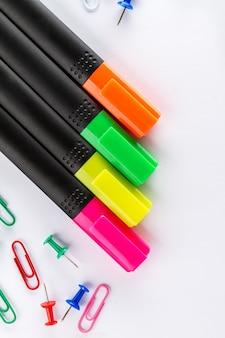 Verschillende kleurrijke markers met kantooraccessoires op witte kantoortafel. bovenaanzicht.