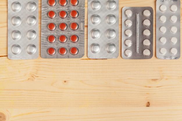 Verschillende kleurrijke pillen in plastic verpakkingen, gestapelde blaren