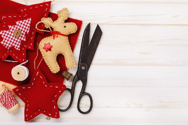 Verschillende knuffels voor kerstvakantie gemaakt door eigen handen bovenaanzicht op de achtergrond van geschenken en gereedschappen met kopieerruimte