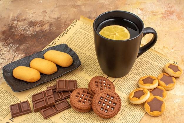 Verschillende koekjes en thee in een zwarte kop en notitieboekje op gemengde kleurentafel