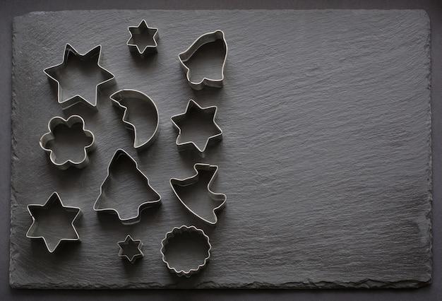 Verschillende koekjessnijders met kerstthema op zwart.