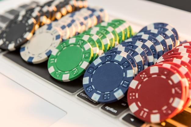 Verschillende kosten casinofiches die op laptop stapelen