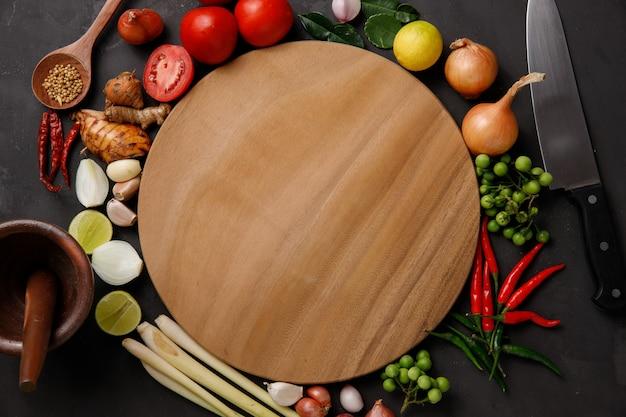 Verschillende kruiden en ingrediënten om te koken op een donkere achtergrond.