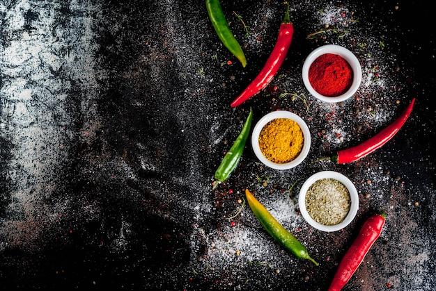 Verschillende kruiden en kruiden. koken . kurkuma, curry, paprika, peper, chili, gedroogde basilicum, zout, verse chili, tijm. zwart roestig metaal. bovenaanzicht,.
