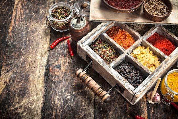 Verschillende kruiden en specerijen in een doos. op een houten tafel.