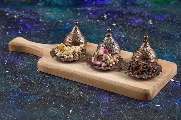 Verschillende kruiden en specerijen op een houten bord