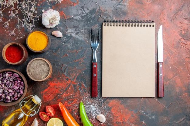 Verschillende kruiden gevallen olie fles bonen en notebook op mix kleurentabel
