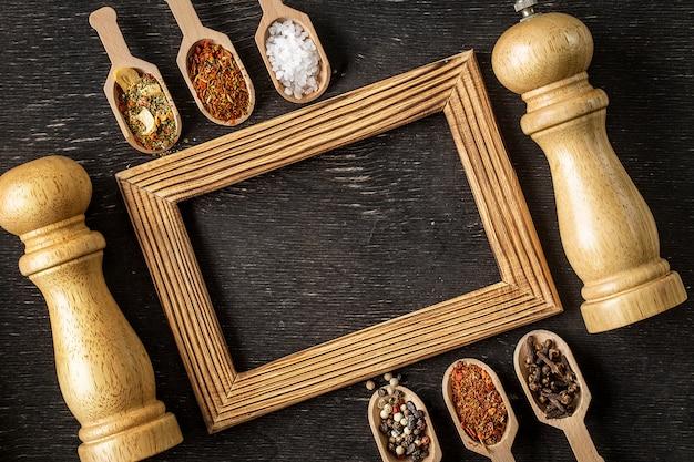 Verschillende kruiden in houten frame met lepels op donkere stenen tafel