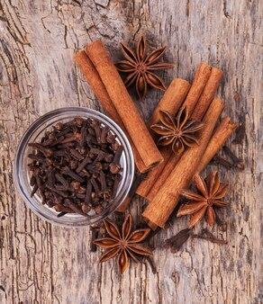 Verschillende kruiden, kaneel, anijs op houten oude tafel