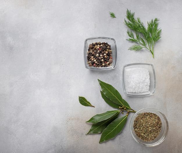 Verschillende kruiden, kruiden, greens, zout en laurier voor het koken van grijs oppervlak, bovenaanzicht