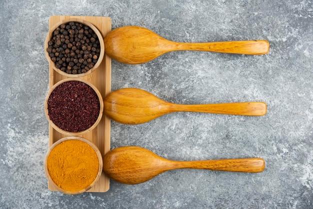 Verschillende kruiden met houten lepels op een grijze tafel.