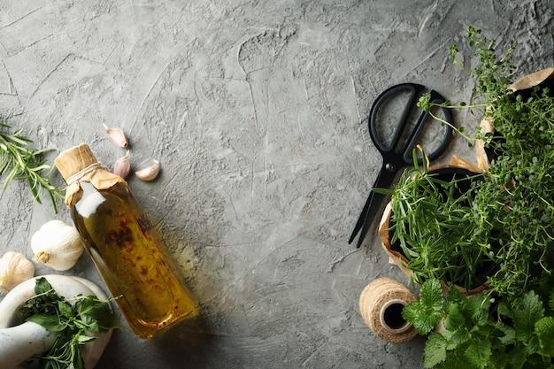 Verschillende kruiden, olie en mortel op grijze achtergrond, ruimte voor tekst