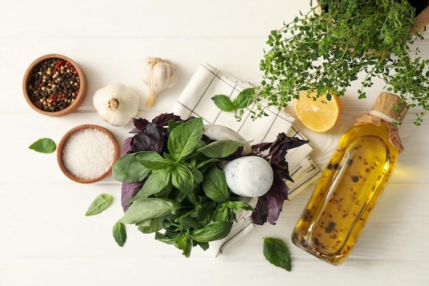 Verschillende kruiden, olie en specerijen op witte houten achtergrond, bovenaanzicht