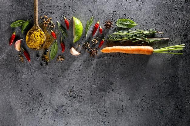 Verschillende kruiden voedselingrediënten houten lepel op grijze tafelachtergrond