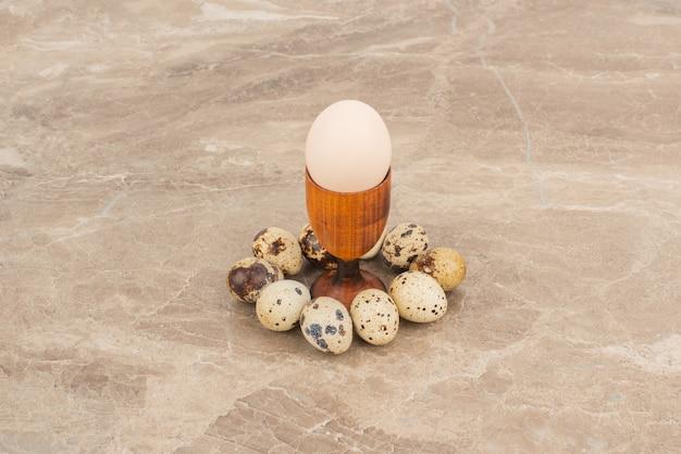 Verschillende kwarteleitjes rond van wit ei op marmeren tafel.