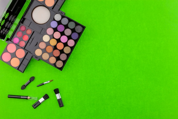 Verschillende make-up borstel, oogschaduw en cosmetica op kleurrijke groenboek achtergrond