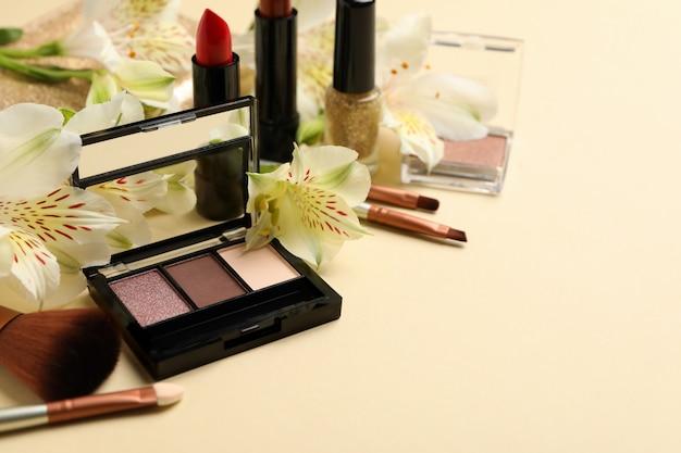 Verschillende make-up cosmetica en bloemen op beige achtergrond. vrouwelijke accessoires