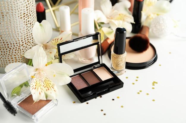 Verschillende make-up cosmetica en bloemen op een witte achtergrond. vrouwelijke accessoires
