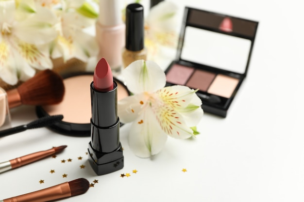 Verschillende make-up cosmetica en bloemen op een witte achtergrond