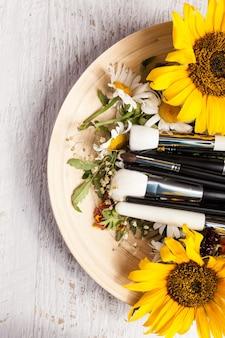 Verschillende make-up penselen op plaat naast wilde bloemen op houten achtergrond