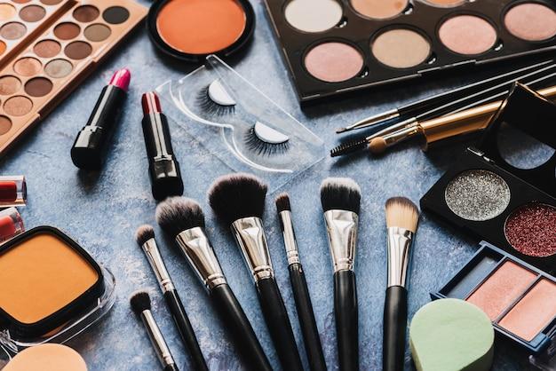 Verschillende make-up producten, borstels op blauwe ondergrond