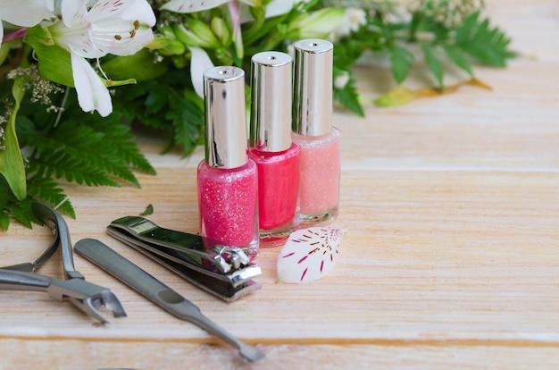 Verschillende manicuretoebehoren op lichte achtergrond. diamant nagelvijl, steen nagelvijl nagelriemverwijderaar, nagelknipper en drie nagellak in roze kleur. kopieer ruimte.