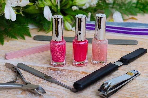 Verschillende manicuretoebehoren op lichte achtergrond. diamant nagelvijl, steen nagelvijl nagelriemverwijderaar, nagelknipper en drie nagellak in roze kleur.