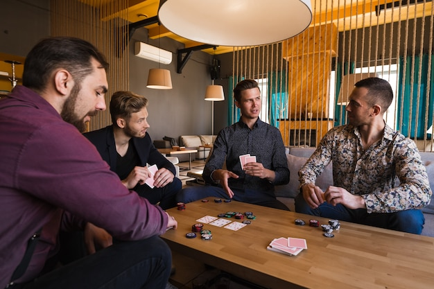 Verschillende mannen spelen poker in een café, met kaarten in hun handen.