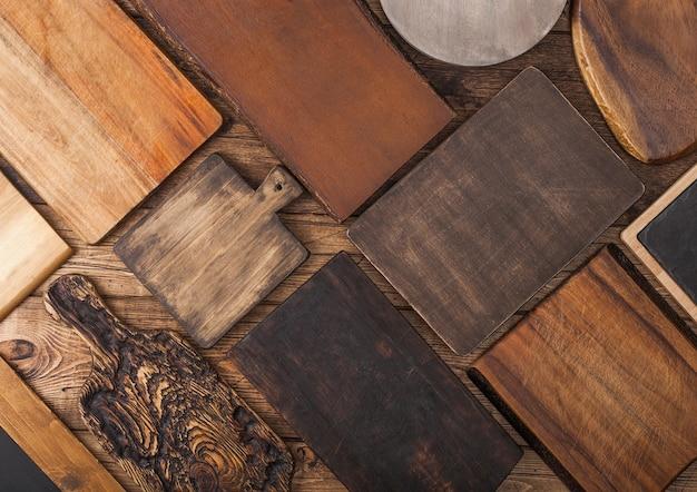 Verschillende maten en vormen keuken snijplanken op hout achtergrond.