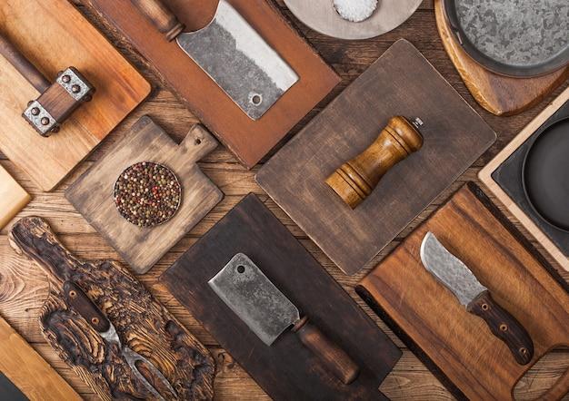 Verschillende maten en vormen keuken snijplanken op houten achtergrond met vleesbijlen, vork en mes en ander keukengerei.