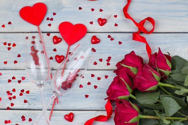 Verschillende maten rode harten, rode rozen en twee glazen