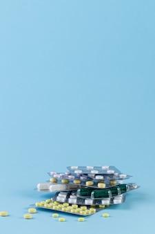 Verschillende medicijnen in tabletten en capsules op blauwe achtergrond. geneeskunde concept. farmaceutische blisterverpakking. pak pillen met tabletten.