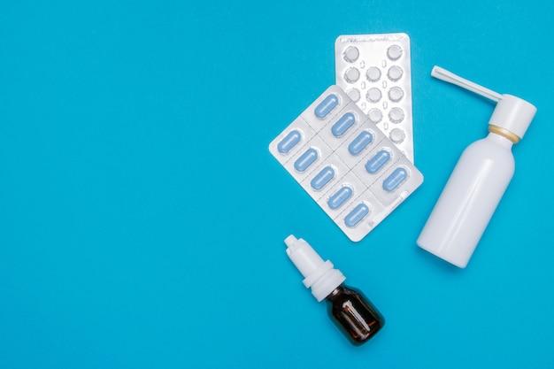 Verschillende medicijnen, sprays van een verstopte neus en pijn in een keel op een blauwe achtergrond.