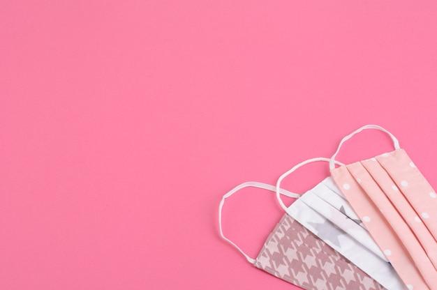 Verschillende medische gezichtsmaskers op roze achtergrond, masker voor apparatuur om de menselijke gezondheid te beschermen tegen griep, coronavirus-infectie, gezondheidszorgconcept, kopie ruimte
