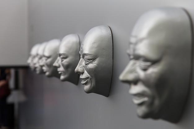 Verschillende menselijke emoties, sculpturaal masker aan de muur. emotieconcept, gezichtsmodellen