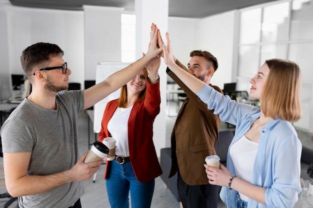 Verschillende mensen high five op het werk