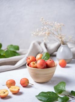 Verschillende mini-appels in een houten kom op een lichte achtergrond
