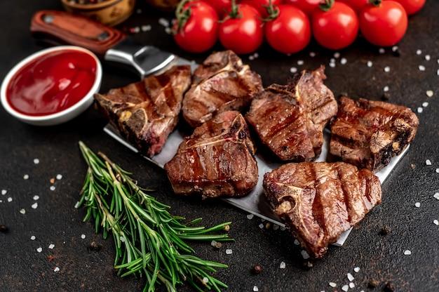 Verschillende mini gegrilde rundvlees t-bone steaks op het mes op stenen tafel