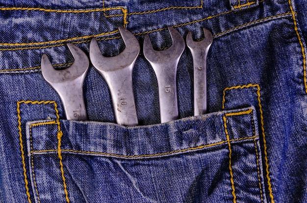 Verschillende moersleutels in een zak van de spijkerbroek. bovenaanzicht