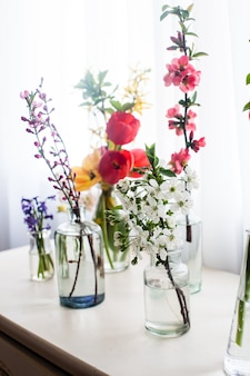 Verschillende mooie bloemen in potten met water op de tafel bij het raam