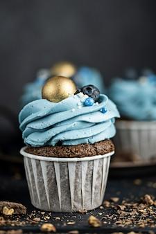 Verschillende muffins of cupcakes met blauw gevormde room en bosbessen op zwarte tafel. rustieke stijl copyspace.