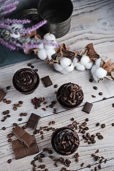 Verschillende muffins of cupcakes met chocoladevormige room aan witte tafel.
