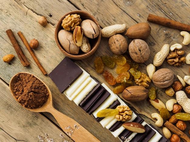 Verschillende noten, chocolade en gedroogd fruit op een houten tafel