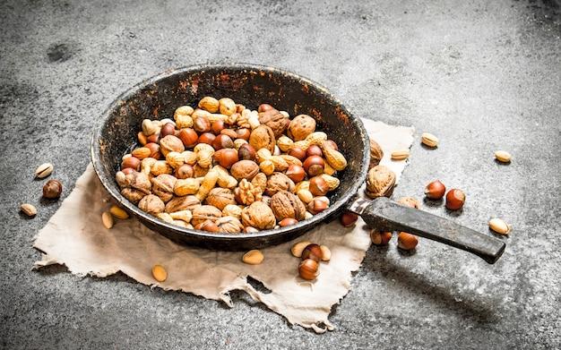 Verschillende noten in een koekenpan op rustieke achtergrond