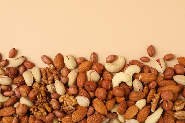 Verschillende noten op beige achtergrond, bovenaanzicht. vitamine voedsel
