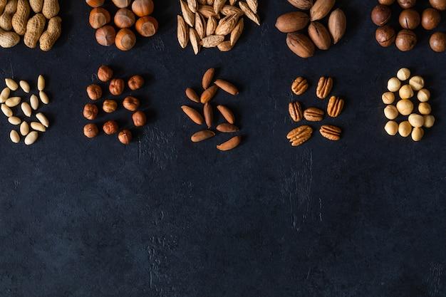 Verschillende noten op zwarte stenen tafel. bovenaanzicht frame met kopie ruimte