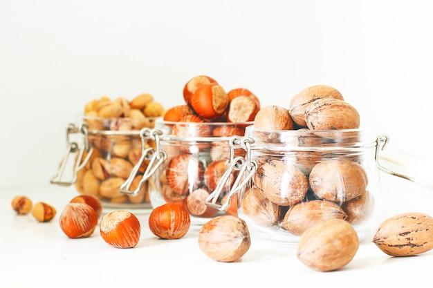 Verschillende noten selectie: hazelnoten, pistache en pecannoten in glazen potten