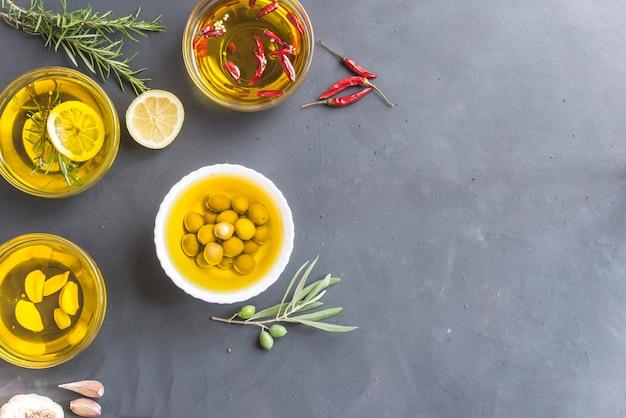 Verschillende oliën met rozemarijn, citroen, chilipepers, knoflook en olijven