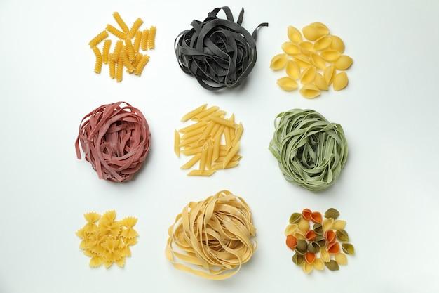Verschillende ongekookte kleurendeegwaren op wit