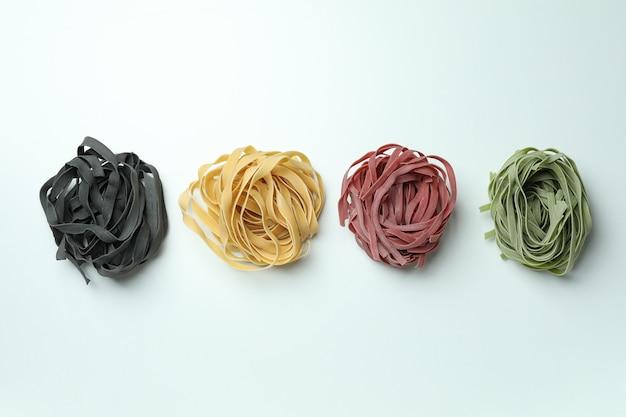 Verschillende ongekookte veelkleurige pasta op wit